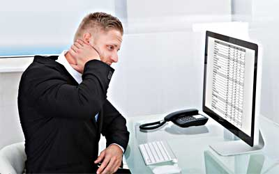 person with hand on face staring at computer screen containing spreadsheet