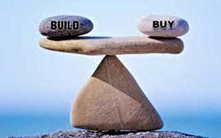 "2 stones labeled ""Build"" and ""Buy"" on either end of flat stone that is balanced on point of triangular stone"