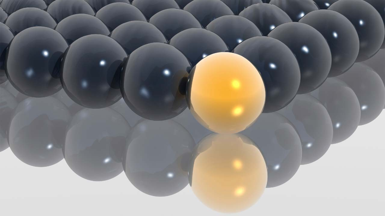 many black balls and one yellow ball all touching on flat surface