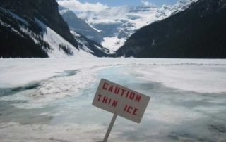 """snowy lake with mountains in background and """"Caution Thin Ice"""" sign sticking out of the ice"""