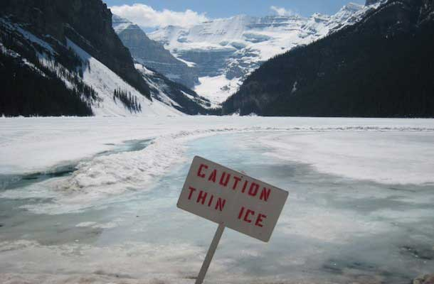 """Caution Thin Ice"" sign on lake"