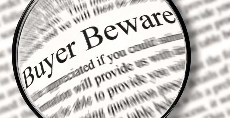 "magnifying glass hovering above newspaper with words ""Buyer Beware"" magnified"